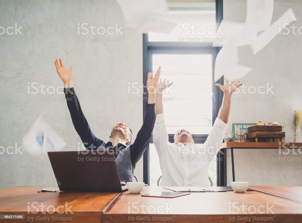 Two of young businessman trowing papers papers/sheets for work after finishing work, successful in business target in modern office, feeling happy, cheerful and relax royalty-free stock photo