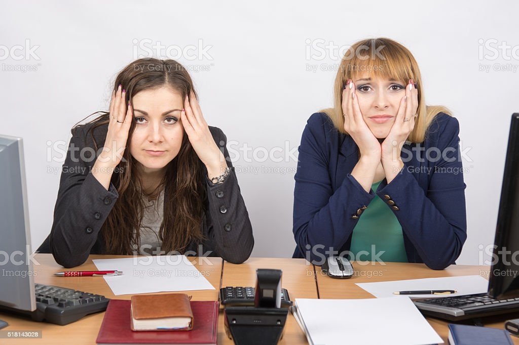 Two office employee sitting with depressed and frightened look stock photo