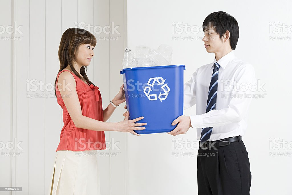 Two office workers holding a recycling bin 免版稅 stock photo