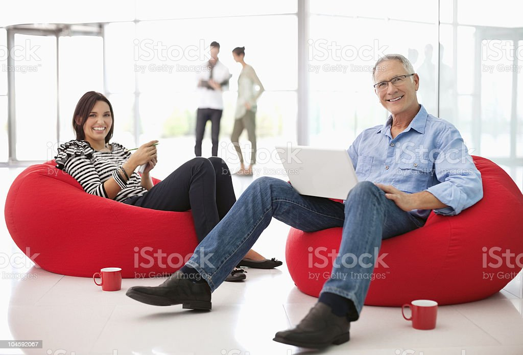 Two office workers on beanbags stock photo