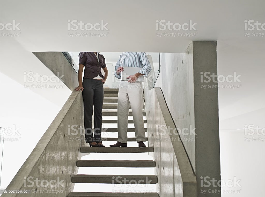 Two office workers standing on stairs, low section royalty-free stock photo