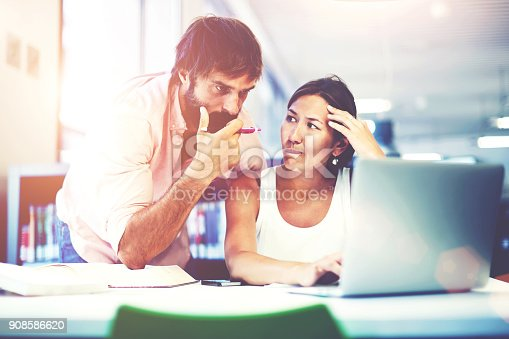 905130626 istock photo Two office workers talking in an office interior, young business colleagues discussing work on a laptop computer in co-working space, corporate business people looking at a laptop having conversation 908586620