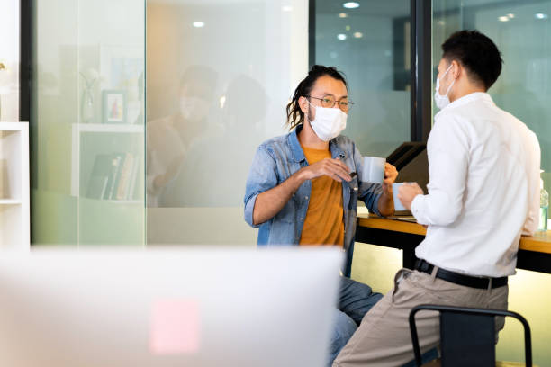 Two office workers talking while coffee break in new normal office. stock photo