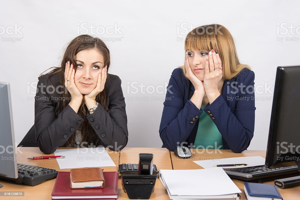 Two office workers tired tortured sitting behind a desk stock photo