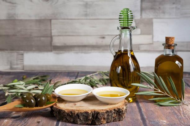 dos botellas de aceite y un puñado de aceitunas en madera - foto de stock