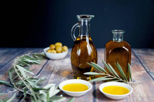 dos botellas de aceite y rama de olivo en negro - foto de stock