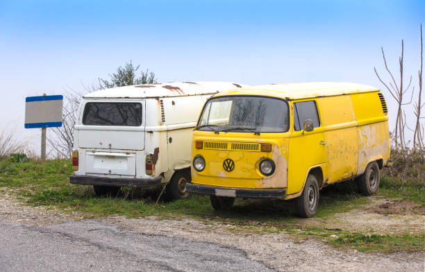 Two old and grunge Volkswagen Beetle vintage van cars parked side by side stock photo