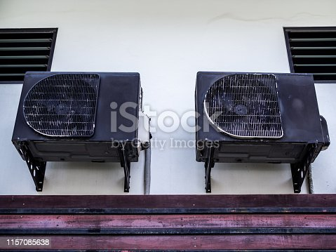 1132460292 istock photo Two old black air conditioner compressors on white wall 1157085638