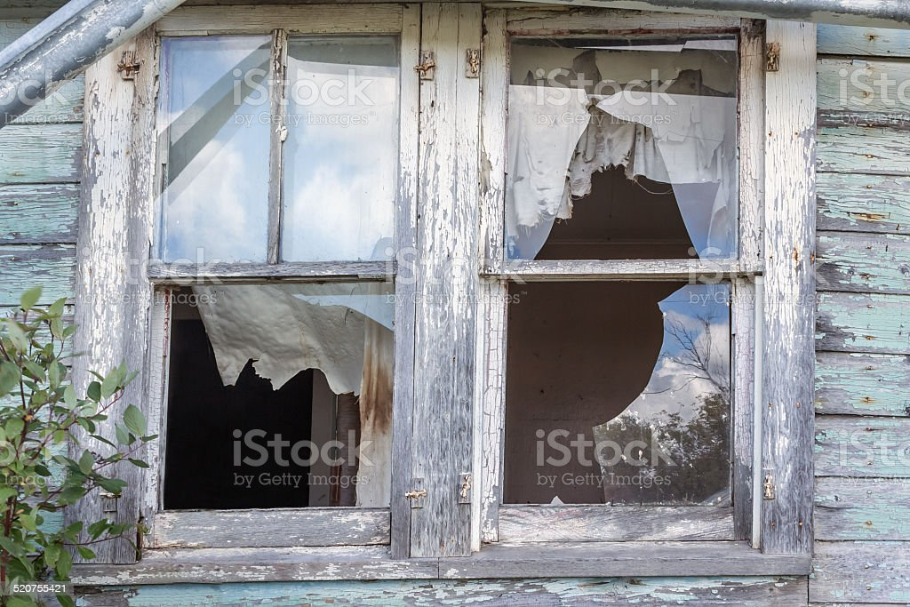 Two old broken windows in an abandoned old house. stock photo