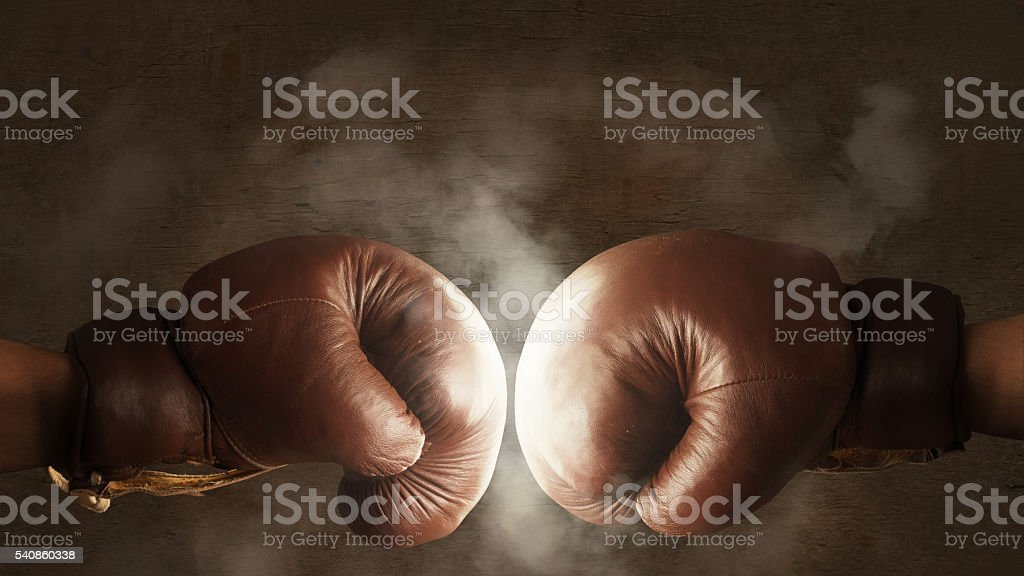 Two old brown boxing gloves hit together stok fotoğrafı
