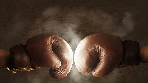 Two old brown boxing gloves hit together stock photo