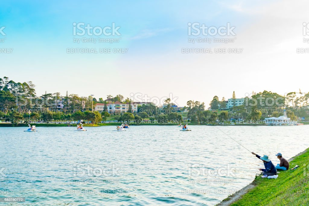 Two old men fishing on the lake in Da Lat Vietnam stock photo