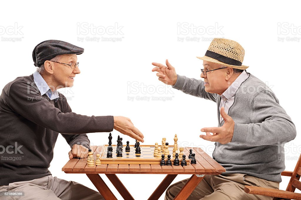 Two old people playing a game of chess stock photo