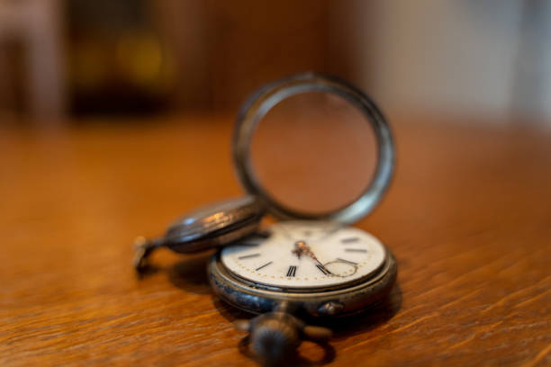 Two old pocket watches are lying on a table stock photo