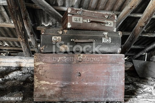 istock Two old, rusty, dusty and dirty brown and black suitcases lying on the brown chest in attic 1047981414