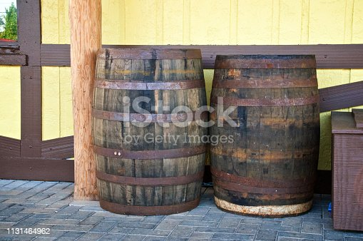 Two old antique wooden whiskey barrels or wine casks are outside against a wall.