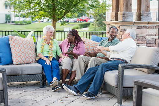 A multi-ethnic group of mature and senior friends hanging out together, sitting outdoors on a patio conversing. The African-American couple are in their 50s. The Caucasian couple are in their 70s. The women are sitting next to each other, talking, and the men are chatting with each other.