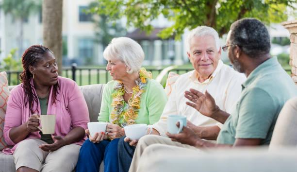 Zwei ältere Paare hängen auf der Terrasse, Gespräch – Foto