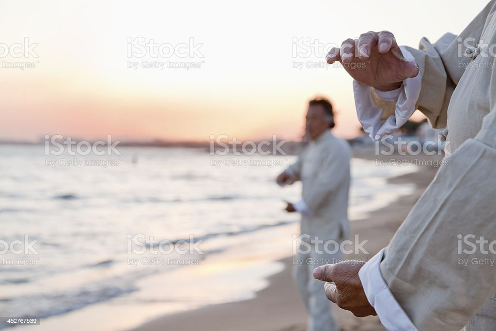 Two older people practicing Taijiquan on the beach at sunset stock photo