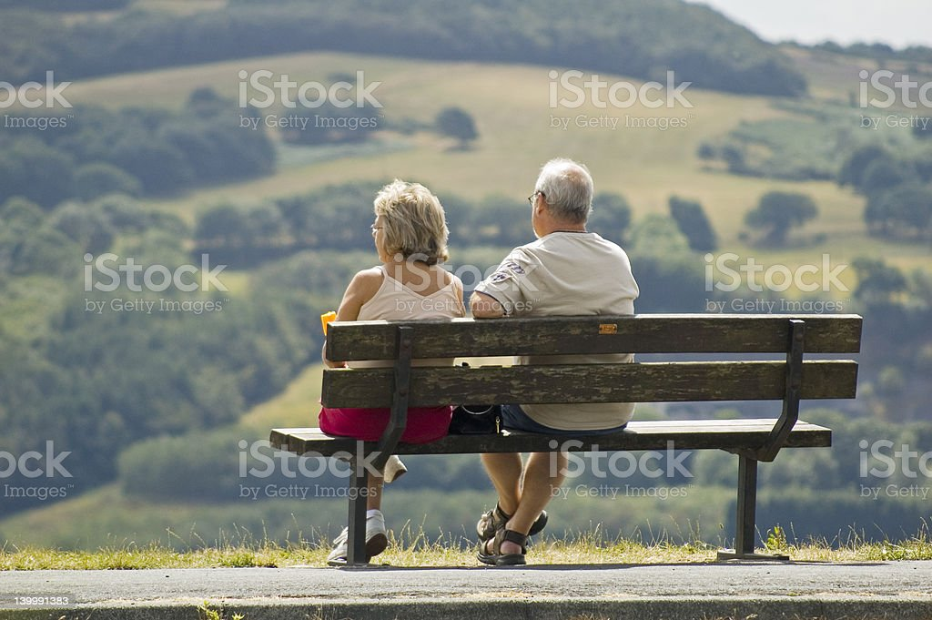 Two older people sitting on a bench royalty-free stock photo