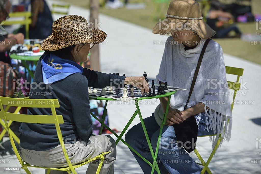 Two older women play chess at a public park stock photo