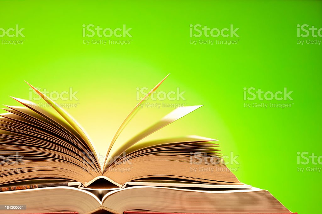 Two opened books on green background royalty-free stock photo