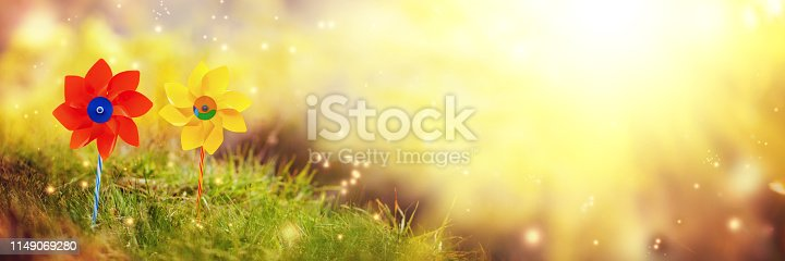 istock Two orange and yellow pinwheels against nature background in sunny summer day. 1149069280