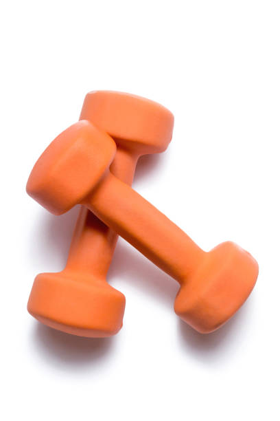 two orange dumbbells lie on top of each other on a white background - weights stock photos and pictures