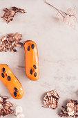 istock Two orange glazed eclairs on white marble table 860614242