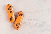 istock Two orange glazed eclairs on white marble table 860614248