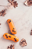 istock Two orange glazed eclairs on white marble table 860614252