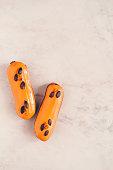 istock Two orange glazed eclairs on white marble table 860614258