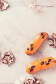 istock Two orange glazed eclairs on white marble table 862079732