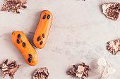 istock Two orange glazed eclairs on white marble table 864415318