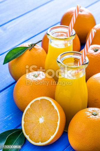 High angle view of two drinking bottles filled with organic orange juice shot on blue table. Whole and sliced oranges are around the orange juice bottles. Predominant colors are orange and blue. High resolution 42Mp studio digital capture taken with Sony A7rii and Sony FE 90mm f2.8 macro G OSS lens