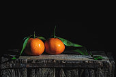 Two orange tangerines with leaves on an old wooden box. Low-key photography.