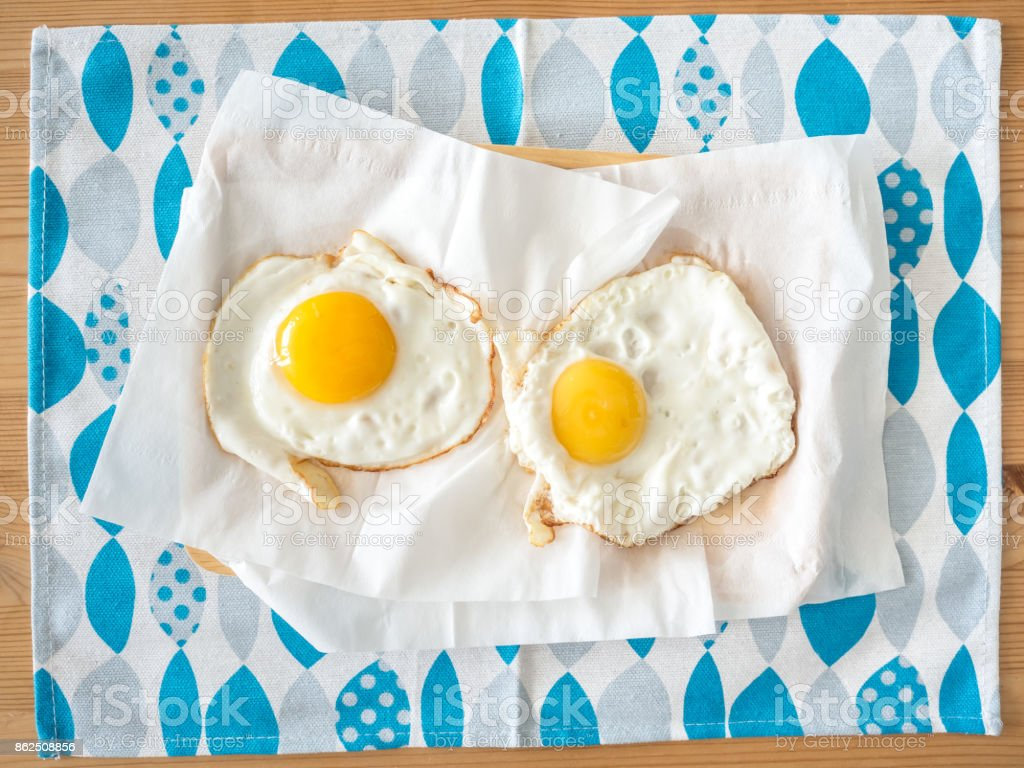 Two ordinaryy fried eggs served on blue sheet. stock photo