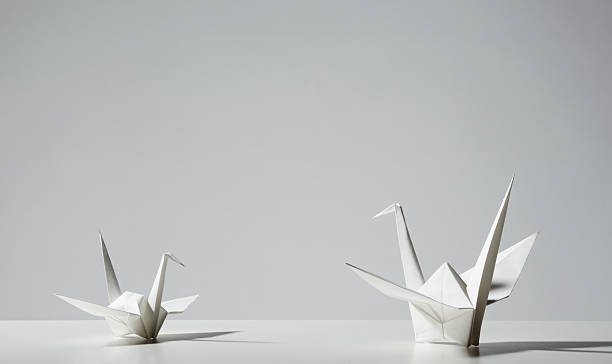 Two origami cranes facing each other on white table  stock photo