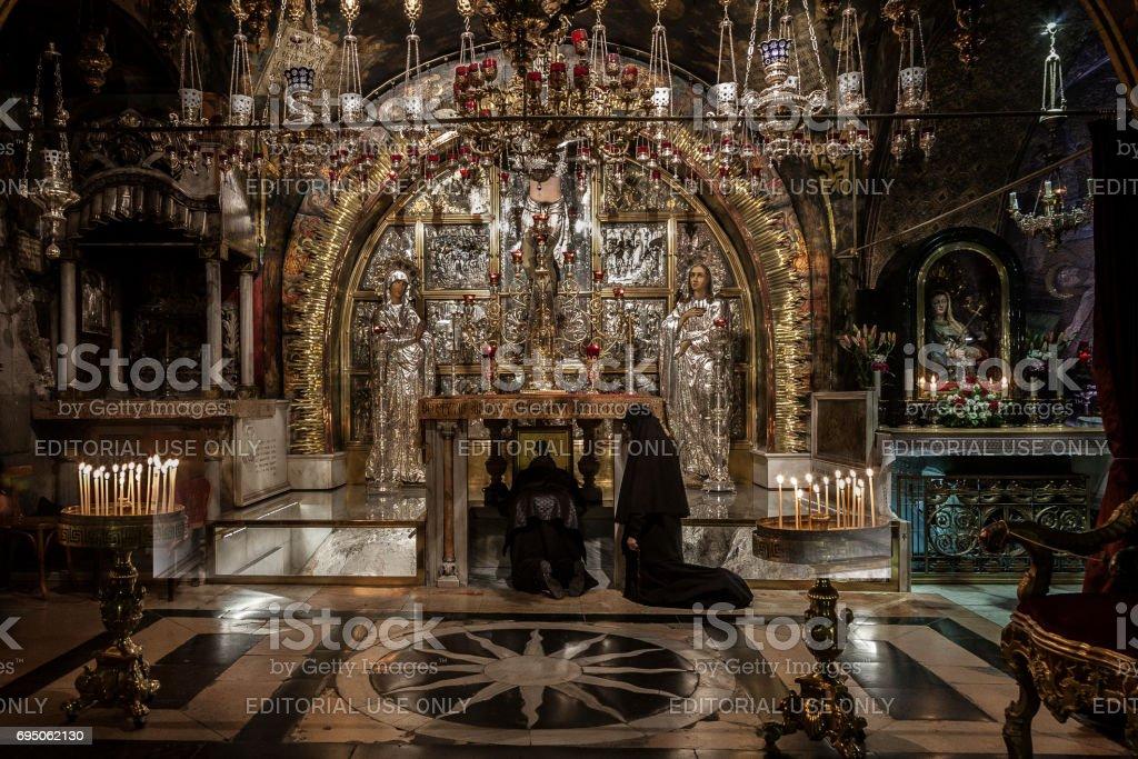Jerusalém, Israel - 26 de dezembro de 2010: Duas freiras da Igreja Ortodoxa rezam de joelhos diante do Altar de crucificações na igreja do Santo Sepulcro em Jerusalém. Esta pedra foi reconhecida como Gólgota (Calvário) onde Jesus Cristo foi crucificado. É um sta XII - foto de acervo
