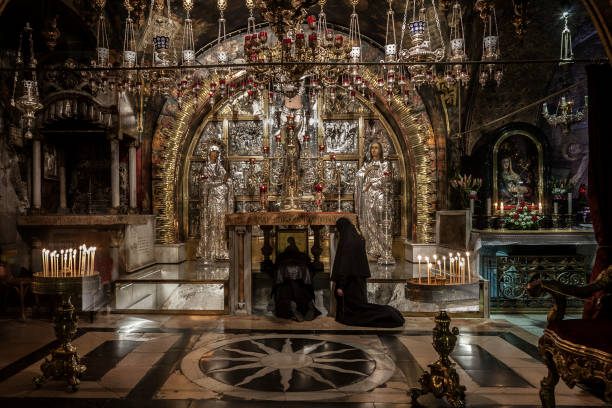 Jerusalem, Israel - December 26, 2010: Two orthodox church nuns pray on their knees in front of the Crucifixions Altar in Holy Sepulchre Church in Jerusalem. This stone was recognized as Golgotha (Calvary) where Jesus Christ was crucified. It is a XII sta stock photo