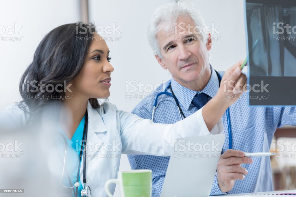 Two orthopedic doctors discuss patient's x-ray stock photo