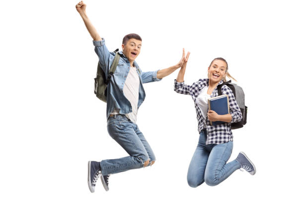 Two overjoyed teenage students in mid-air high-fiving each other stock photo