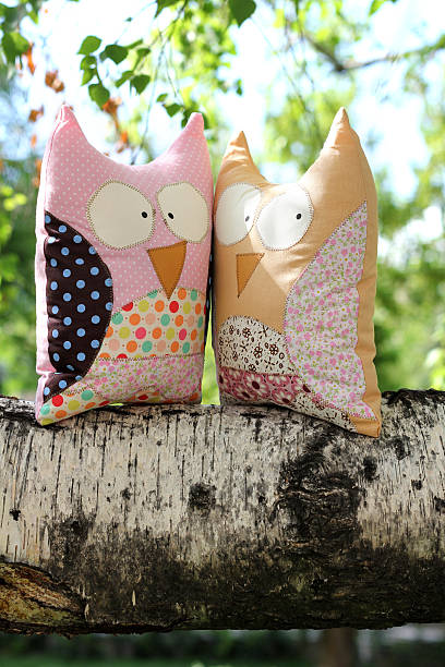 Two owl toys on a branch stock photo