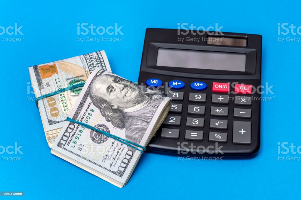 Two packs of folded dollar bills with calculator on a blue background. Business concept. stock photo