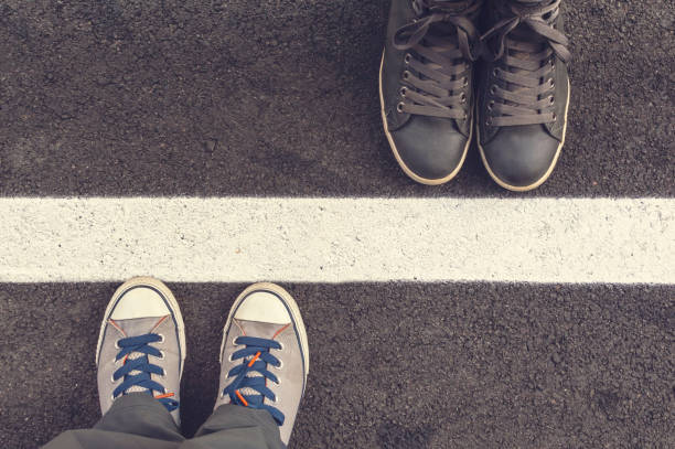 two pair of sneakers on a asphapt road. - 地理的境界 ストックフォトと画像