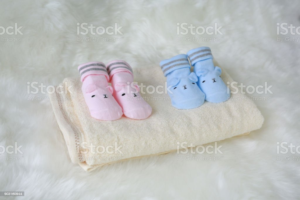 Two pair of Socks and towel for newborn babies on the white fur background. stock photo