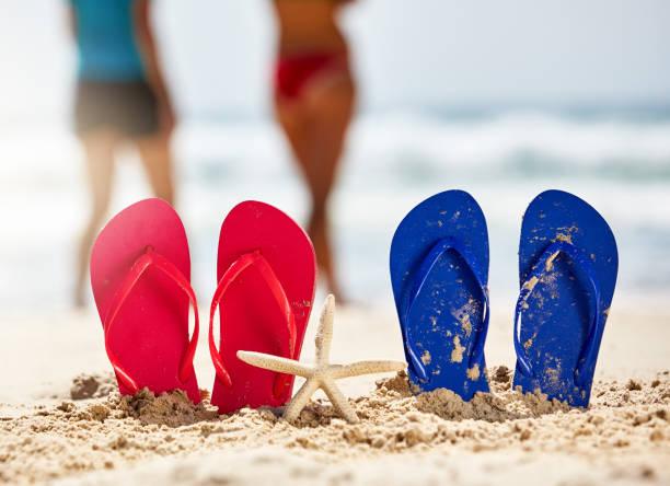zwei paare von erwachsenen strandsandalen am strand, menschen, die hinter - flitterwochen flip flops stock-fotos und bilder