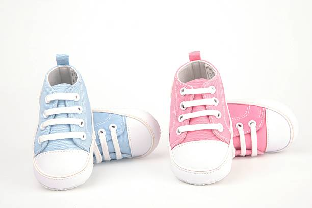 two pairs of baby shoes, one pair blue and one pair pink - its a girl stock photos and pictures