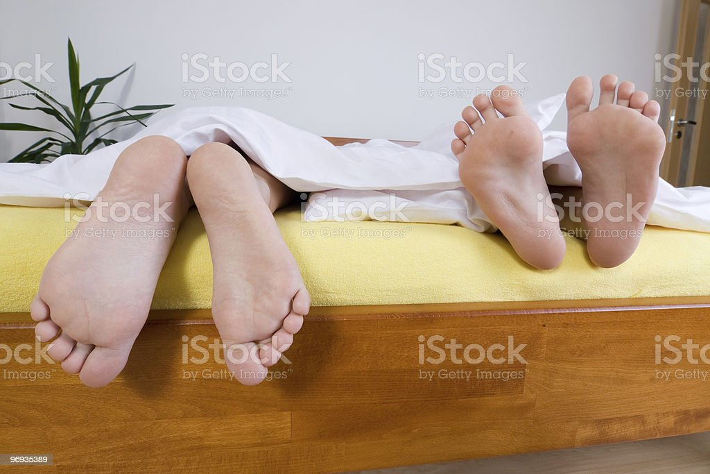 Two pairs of feet in bed royalty-free stock photo