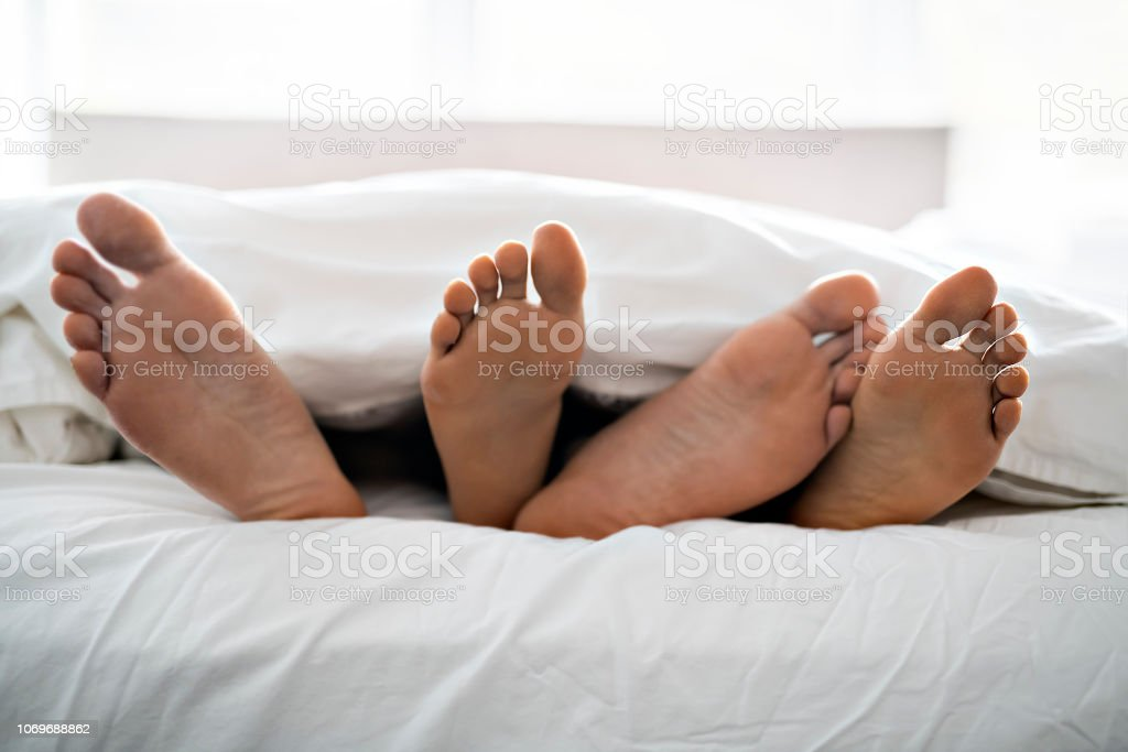 A two pairs of feet under duvet couple makes love in bed